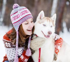 Junge Frau mit Hund im Schnee